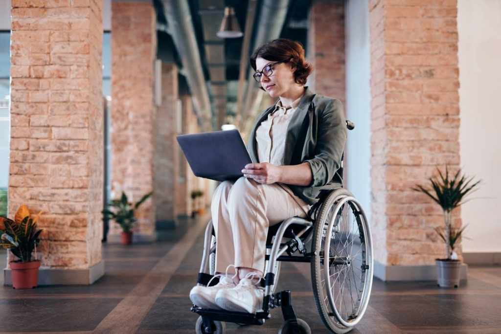 Woman on wheelchair using a laptop